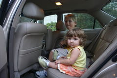 On the road. Two kids on the back seat of a car Royalty Free Stock Images