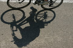 On the road. The shadow of a cyclist Stock Photo