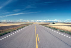 ROAD. In Montana , Harvest, empty   with visible harvest equipment on field Stock Photo
