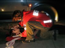 Road accident. MD/paramedic is helping hurt victim of accident royalty free stock photo