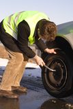 Road accident. Driver in reflective safety vest changing the car wheel Stock Photo