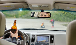 Road accident due to alcohol about to happen. Road accident due to alcohol about happen as  drunk female driver clutching her bottle  booze  one hand while Royalty Free Stock Photo
