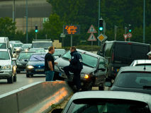 Road accident with police and driver. Traffic acident with polic agent talking with driver Royalty Free Stock Image