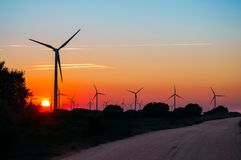 Road across sun and silhouettes of wind generators Stock Photo