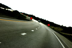 On the road again. Curved road with two construction signs on either side of the road in the distance Stock Photography