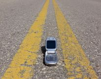 On the Road Again. Cell phone laying between solid yellow lines on the highway royalty free stock photos