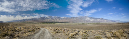 On the road again. Road to the mountain accross the california desert Royalty Free Stock Photo