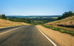 Road against hilly landscape Stock Photos