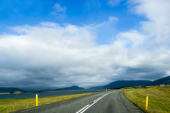 Road against mountain background, Iceland, cloudy summer weather Stock Photos