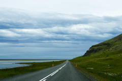 Road against mountain background, Iceland, cloudy summer weather Royalty Free Stock Images