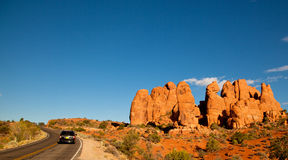 Road against red rock formation Stock Images