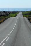 Road ahead. Curvy road in lava heading towards the sea Royalty Free Stock Images
