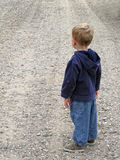 Road ahead. Child looking down the gravel road ahead stock photography