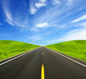 Road Ahead. The Straight Road Ahead, flanked by green fields Royalty Free Stock Images