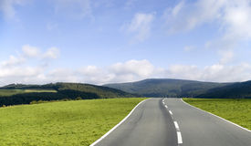 The road ahead. An asphalt road through the grass hills of the country stock images