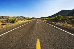Road ahead. With mountains and hills on both sides with a clear sky horizon at far Royalty Free Stock Image