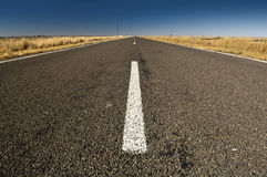 Road Ahead. On a wide country asphalt road with blue sky Royalty Free Stock Photography