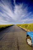 Road ahead. Road to nowhere. A car about to runaway on an old road, over the blue sky Stock Image