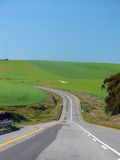 The Road Ahead Cuving to the Left. The Winding Road Ahead, flanked by green fields stock photos