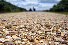 The road ahead. A low shot of a gravel road Stock Image