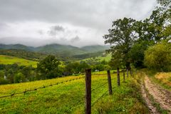 Road along the fence in rural outskirts. Pasture behind the barbwire. mountainous countryside on a dull day with overcast sky. village down in the valley. some Stock Photos