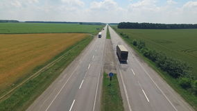 Road along which the trucks are traveling. The drone flies over the road along which the trucks are traveling, gradually catching up with the camera. The road stock video