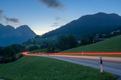 Alpine road with traffic light trail Stock Photo