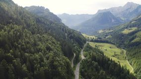 Road in alps. Aerial view mountain and forest landscape of alps with mountain road stock footage