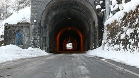 Road with ancient stone tunnel in winter scenic. Bielmonte, Italy - March 3, 2018: Road with ancient stone tunnel in winter scenic with icicles and snow stock video footage