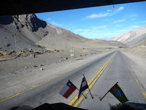 Road at andean pass seen from window of a truck with flags Royalty Free Stock Photography