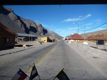 Road at andean pass seen from window of a truck with flags Stock Image