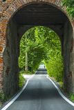 Road through arch in Italy. Mirazzano (Milan, Lombardy, Italy), road through arch and old man with bicycle Stock Images