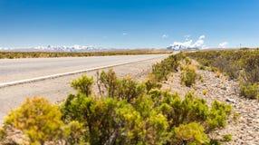 Road asphalt tawards mountains range ridge, Bolivia landscape. Royalty Free Stock Images