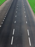 Road  asphalted  highway. The asphalted road of highway with white lines of a marking and lawns on roadsides Royalty Free Stock Image