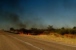 Road of Australia, bush fire. Road of Australia with huge bush fire in background, smoke and blue sky stock photo