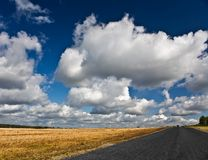 Road on the autumn field with cloudy sky Stock Photo