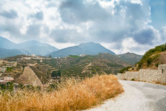 The road on the background of mountains and sky with storm cloud. S on the island of Crete, Greece Stock Photos