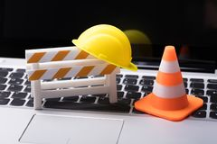 Road Barrier With Hard Hat And Traffic Cone. On Laptop Keypad stock images