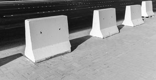 Road barrier. White concrete blocks stand on roadside stock photography
