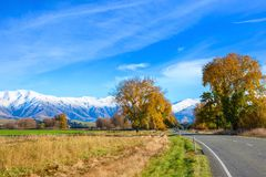 A road with a beautiful view at the entrance to the snow-capped mountains on the sunny autumn morning, Canterbury, South Island, N. Ew Zealand stock images