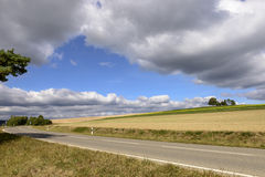 Road bending under thick clouds on fall fields, Germany Stock Photo