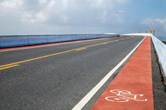 Road with bicycle lane on bridge over the river Stock Images