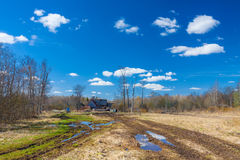 Road with big puddle on the field on countryside toward to wooden house and blue sky reflection in puddles Stock Photo
