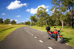 Road bike. Red motorbike on side of winding road Royalty Free Stock Image