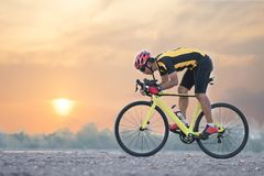 Road bike cyclist man cycling. Biking sports fitness athlete riding bike on an open road to the sunset. stock image