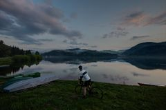 road bike driver looking to beautifull lake with clouds and reflection royalty free stock photo