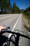Road Biking. This is a picture of a biker mountain biking down a road with a view of the ocean and a mountain with pine trees Royalty Free Stock Images
