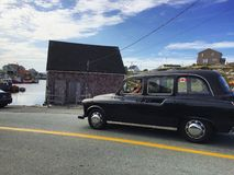 Old car driving by seaside town. Road black vehicle north america cove royalty free stock images