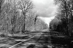 Road black and white. A village road in through a forest leading to Perouges in France Stock Photos