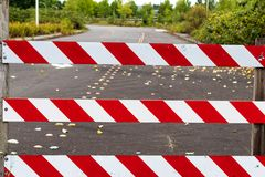 Road block barricade sign stripes. White and red with road behind royalty free stock photo